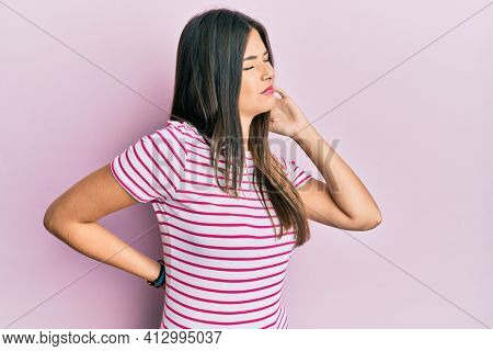 Young brunette woman wearing casual clothes over pink background suffering of neck ache injury, touching neck with hand, muscular pain