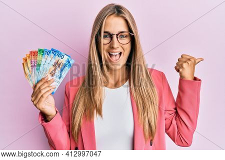 Young blonde woman wearing business style holding swiss franc banknotes pointing thumb up to the side smiling happy with open mouth