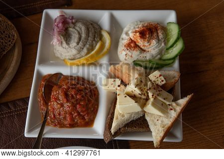 White Crockery Plate With Mezze Tasting Set Of Assorted Pate Pastes And Appetizers Made From Mashed