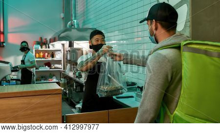 Young Man Chef Giving Food Delivery Food. Takeaway Food Delivery During Self-isolation. Restaurant S