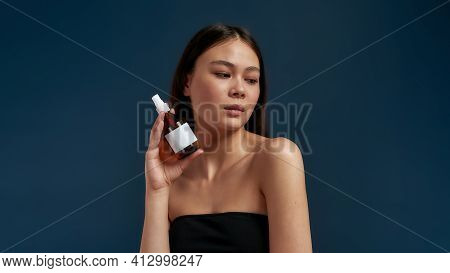 Young Girl Standing With A Bottle Of Body Care Products. Personal Care And Healthy Lifestyle. Clean