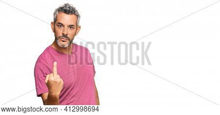 Middle age grey-haired man wearing casual clothes showing middle finger, impolite and rude fuck off expression