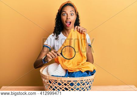 Young african american girl holding magnifying glass looking for stain at clothes afraid and shocked with surprise and amazed expression, fear and excited face.