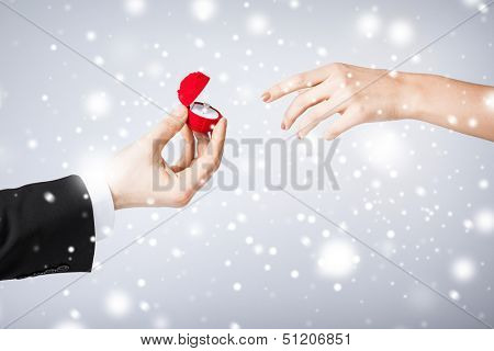 love, romance, marriage, jewelry concept - couple hands with wedding ring and gift box