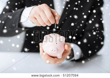 money, cash, finances, savings, banking concept - man putting coin into small piggy bank