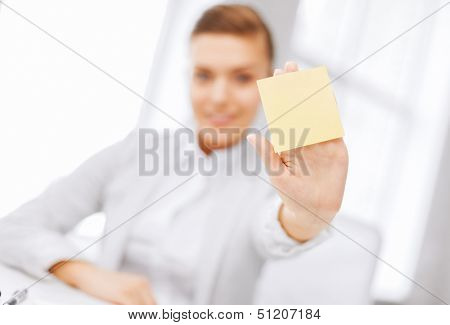 business, office, school and education concept - smiling businesswoman showing blank sticky note