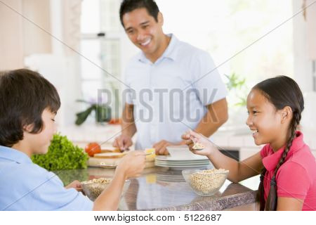 Children Having Breakfast While Dad Prepares Food