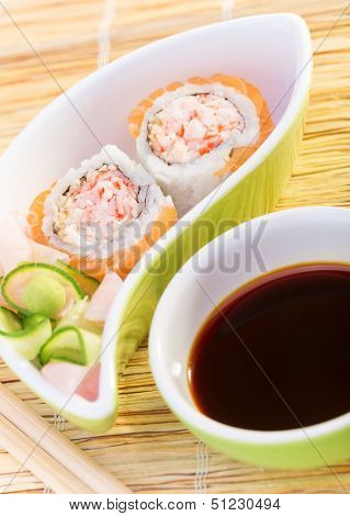 Tasty prepared sushi with avocado, cucumber, crab and salmon, eating by wooden chopsticks, served with soy sauce and ginger, healthy food