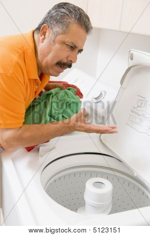 Laundry Man Chores Confused Domestic Frustrated Cleaning 50s Fifties Middle Aged Annoyed Casual Clothing Color Colour Image Confusing Domestic Life Frustration Gesturing Holding Home Housework Indoors Inside Latin American Latino Hispanic Laundry Room One poster