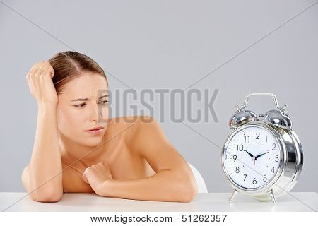 Beautiful young woman looking at a large silver retro alarm clock with bells in consternation as though waiting for it to ring