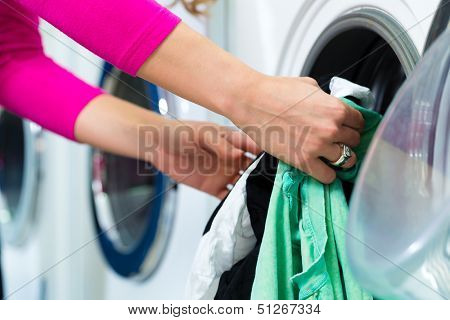 Young woman in a launderette, washing her dirty laundry, in the background are washing machines