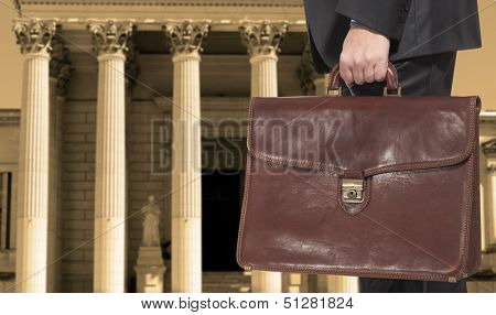 A lawyer with a briefcase on the background of the courthouse