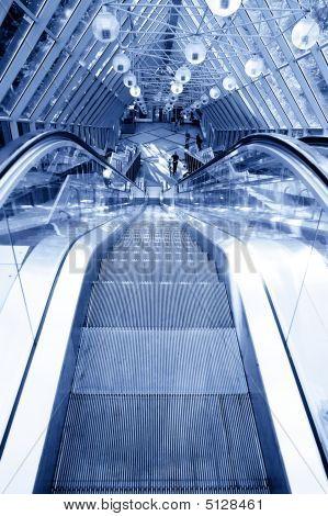 Menschen stehen auf Rolltreppe in modernen Businesscenter