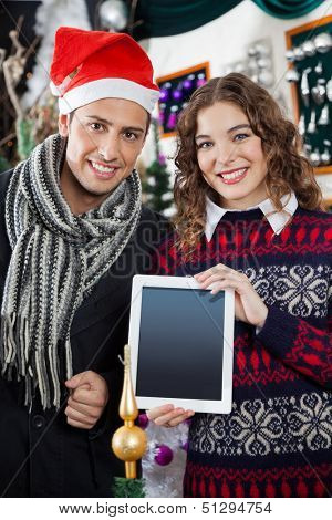 Portrait of happy young couple showing digital tablet while standing at Christmas tore