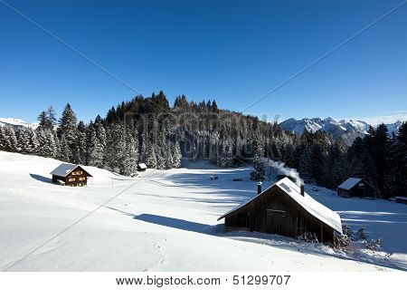 Rural Sunny Winter Landscape With Occupied Log Cabins In The Mountains