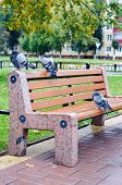 Three pigeons sitting on a bench on the background of autumn leaves poster