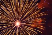 Explosion of golden firework in the night sky poster