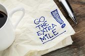 go the extra mile - motivational slogan on a napkin with a cup of coffee poster