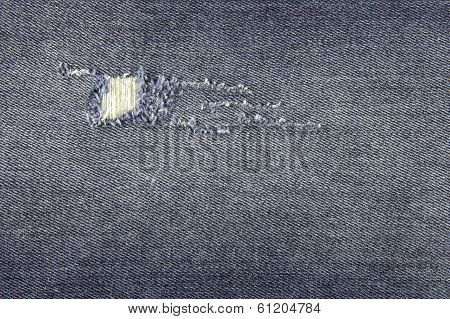 Worn blue jeans with a hole for background or texture poster