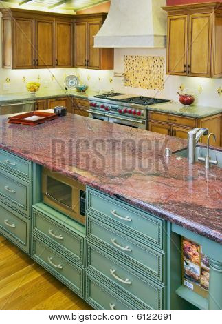 A Luxury Kitchen With a Red Granite Island