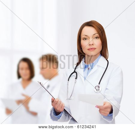 healthcare and medicine concept - calm female doctor with clipboard and stethoscope