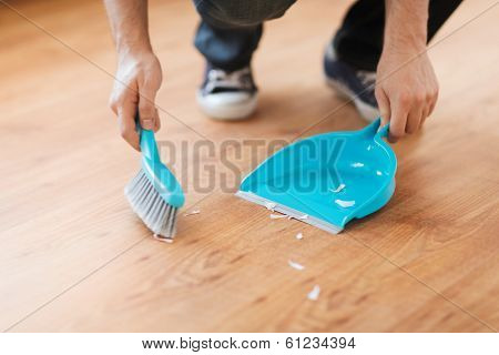 cleaning and home concept - close up of male brooming wooden floor with small whisk broom and dustpan