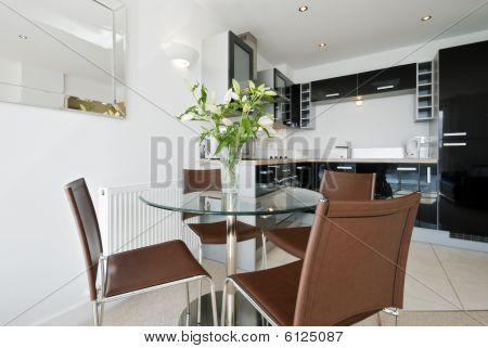 open plan kitchen with dining table and four seats