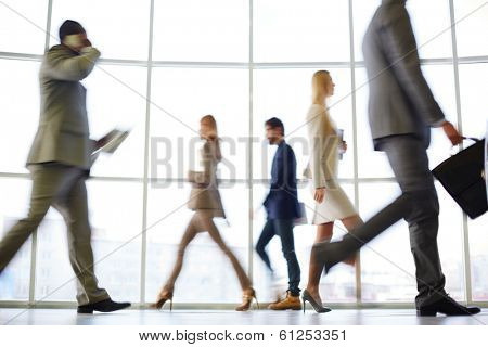 White collar workers going down office corridor at the end of working day
