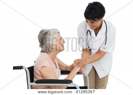 Female doctor talking to a senior patient in wheelchair over white background