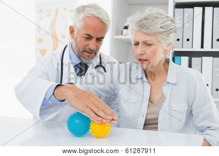 Male doctor with senior patient using stress buster balls at the medical office