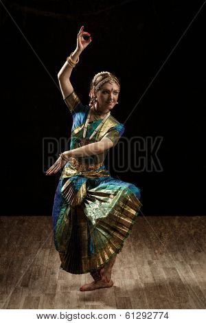 Vintage retro style image of young beautiful woman dancer exponent of Indian classical dance Bharatanatyam in Shiva pose