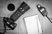 Photography equipment including a professional digital SLR camera and light meter with a blank notebook poster
