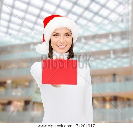 christmas, holdays, people, advertisement and sale concept - happy woman in santa helper hat with blank red card over shopping center background