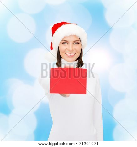 christmas, holdays, people, advertisement and sale concept - happy woman in santa helper hat with blank red card over blue lights background