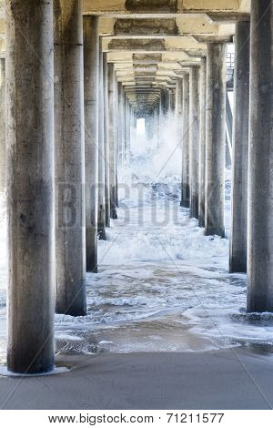Waves generated by a storm rush through the underside of a pier, creating rough, turbulent water as it moves through the pillars to the beach.