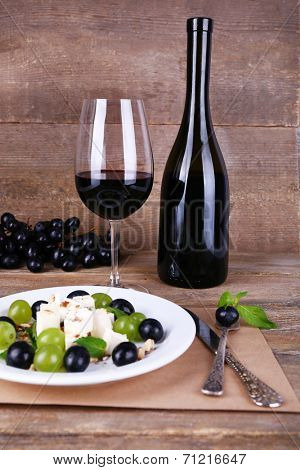 beautiful still life with wine and salad on wooden background
