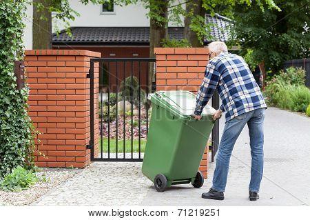 Man Is Pushing Wheeled Dumpster