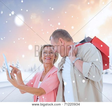 Couple with shopping bags and tablet against snowy landscape with fir trees poster
