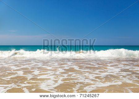 Waves crashing on beautiful sandy beach on sunny day in Sri Lanka.