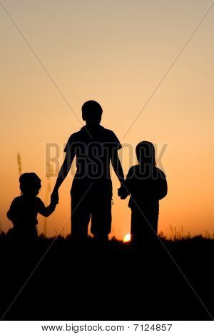 mother and children - silhouette by sunset