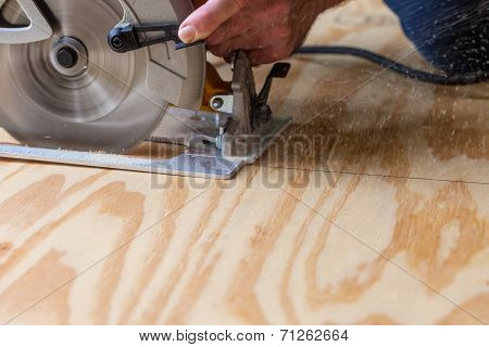 Man using a circular saw to cut plywood poster