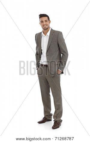 Handsome businessman standing in grey suit, hands in pocket.