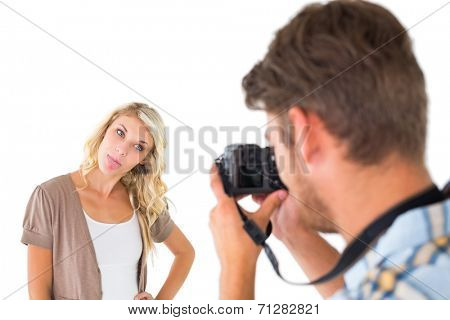 Man taking photo of his girlfriend sticking her tongue out on white background