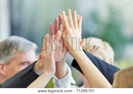 Many cheering hands giving High Five in the business office