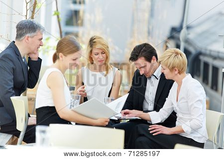 group of business people working in team outdoors in a coffee shop