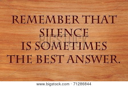 Remember that silence is sometimes the best answer - an old saying on wooden red oak background poster