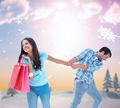 Happy couple with shopping bag against snowy landscape with fir trees poster