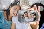 Hand holding smartphone showing close friends smiling at camera poster