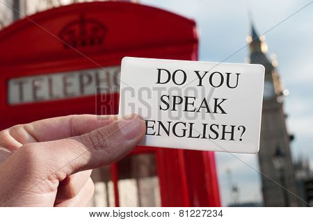 a man holding a signboard with the text do you speak english? with a red telephone booth and the Big Ben in the background, in London, UK