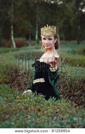 Elegant Young Woman Dressed Like Queen Walking In Garden